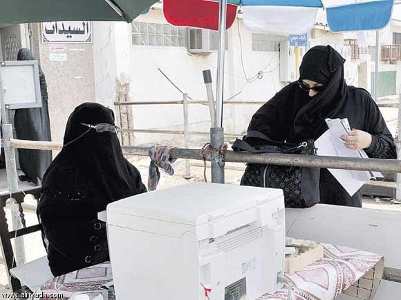 مواطنة تقف أمام القسم النسائي في الجوازات لتعبئة نماذج تجديد إقامة أبنائها